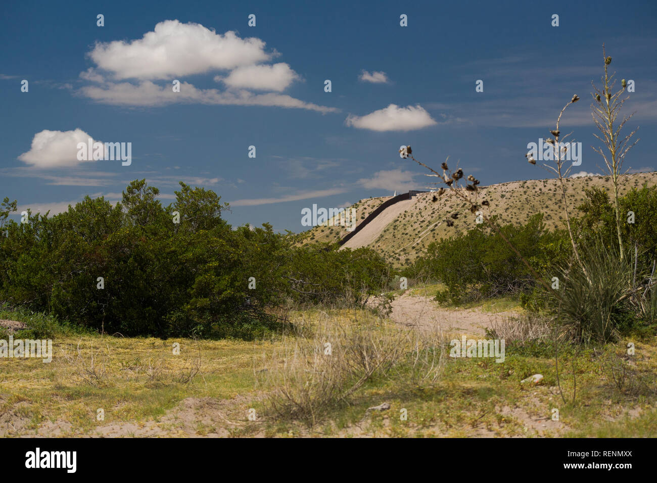 The US-Mexico Border Fence along a Steep Hill in Sunland Park, New Mexico near El Paso, Texas with Train Tracks in the Foreground Stock Photo