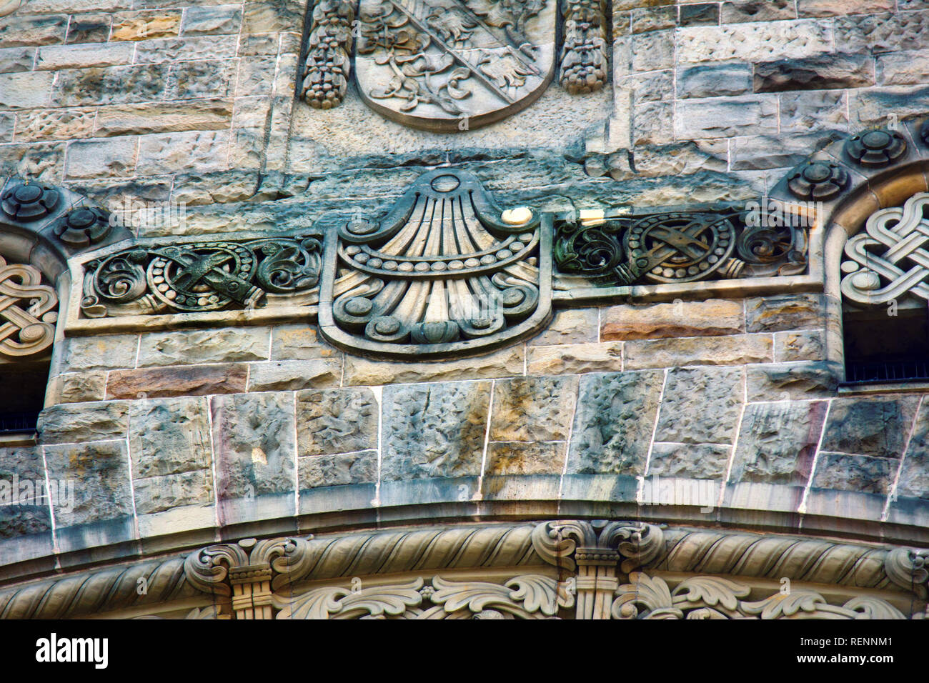 Arabesques of plants, lilies, wreaths, circles, crossed swords encircle the monumental building in Metz. Stone carving - Stock Image