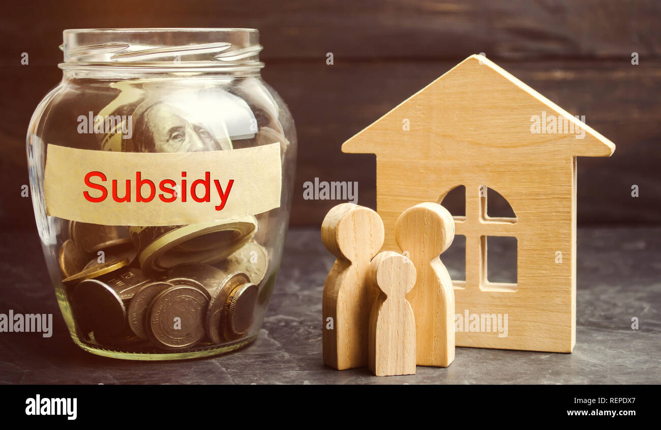 The family is standing near a glass jar with the inscription Subsidy. Financial aid, support to the population. Cash grants, interest-free loans. Tax  - Stock Image