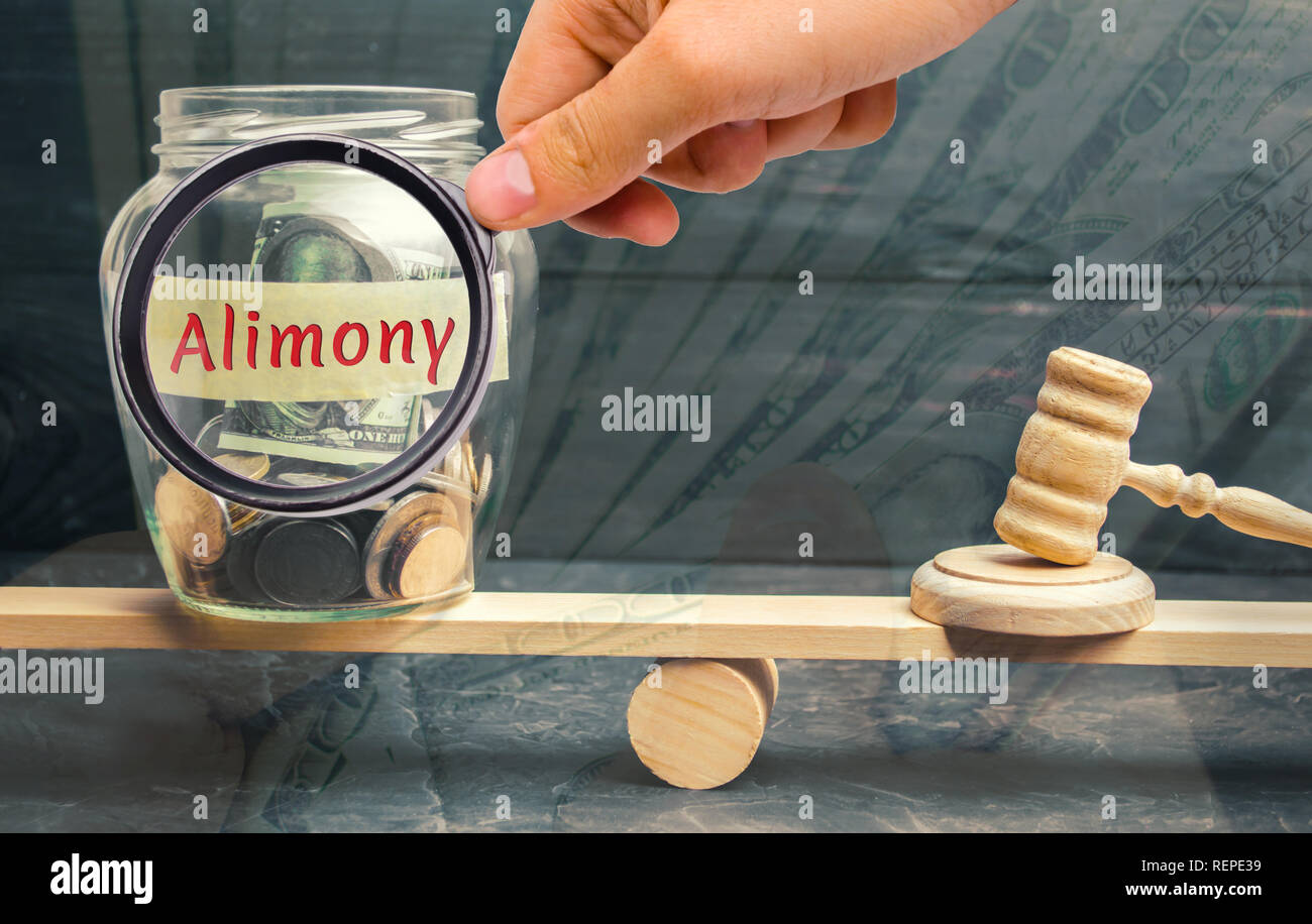 Glass jar and the inscription 'Alimony' and the hammer of the judge are on the scales. Payment of alimony of one of the spouses. Debt. Child custody.  - Stock Image