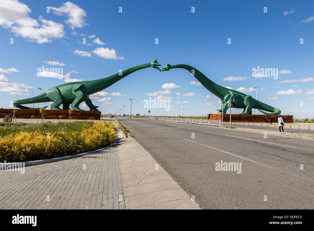 Erenhot, Inner Mongolia, China - September 23, 2018: Two green kissing dinosaurs. Statues of two dinosaurs, located on both sides of the road. - Stock Image