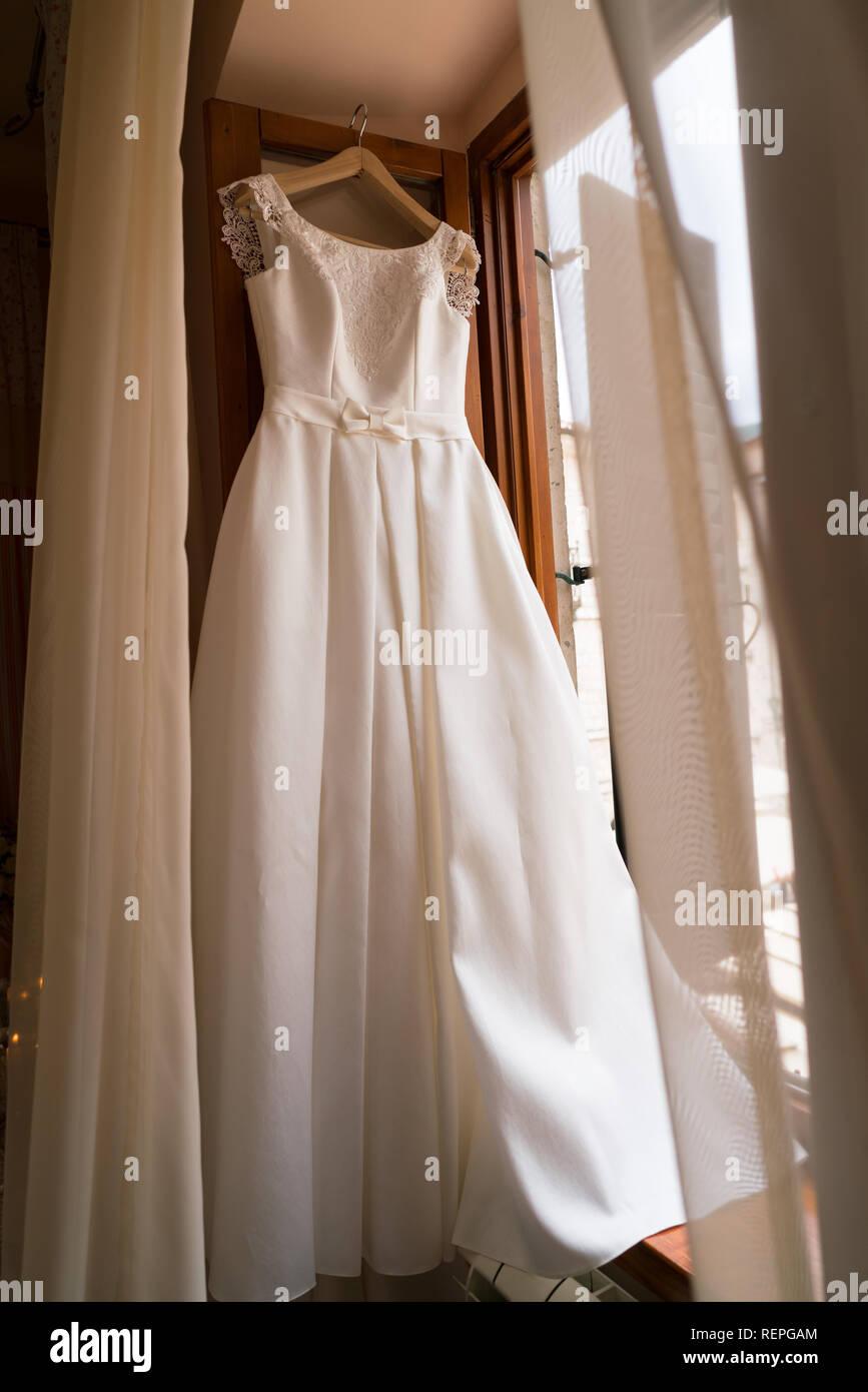 white wedding dress hanging on a hanger - Stock Image