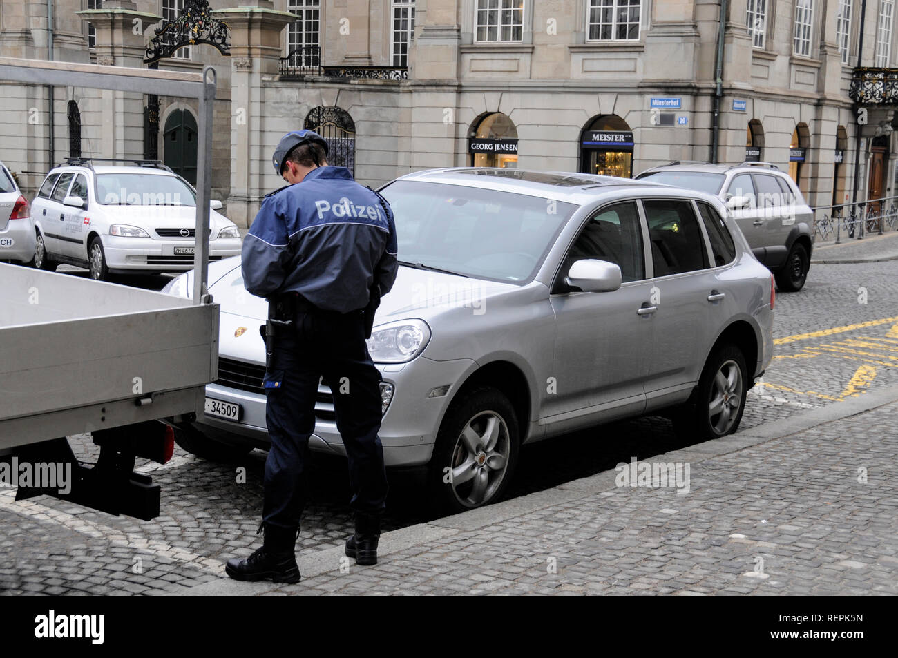 A police officer books a parked car in Zurich, Switzerland - Stock Image