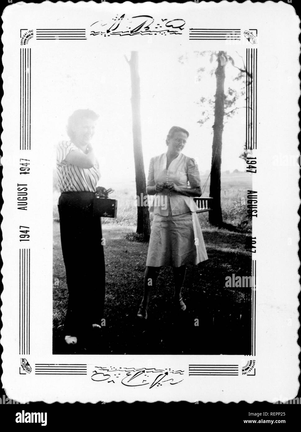Two women stand in an outdoor setting among trees, posing and smiling, as one woman prepares to take the other woman's photograph using a Kodak Brownie box camera, August, 1947. () - Stock Image