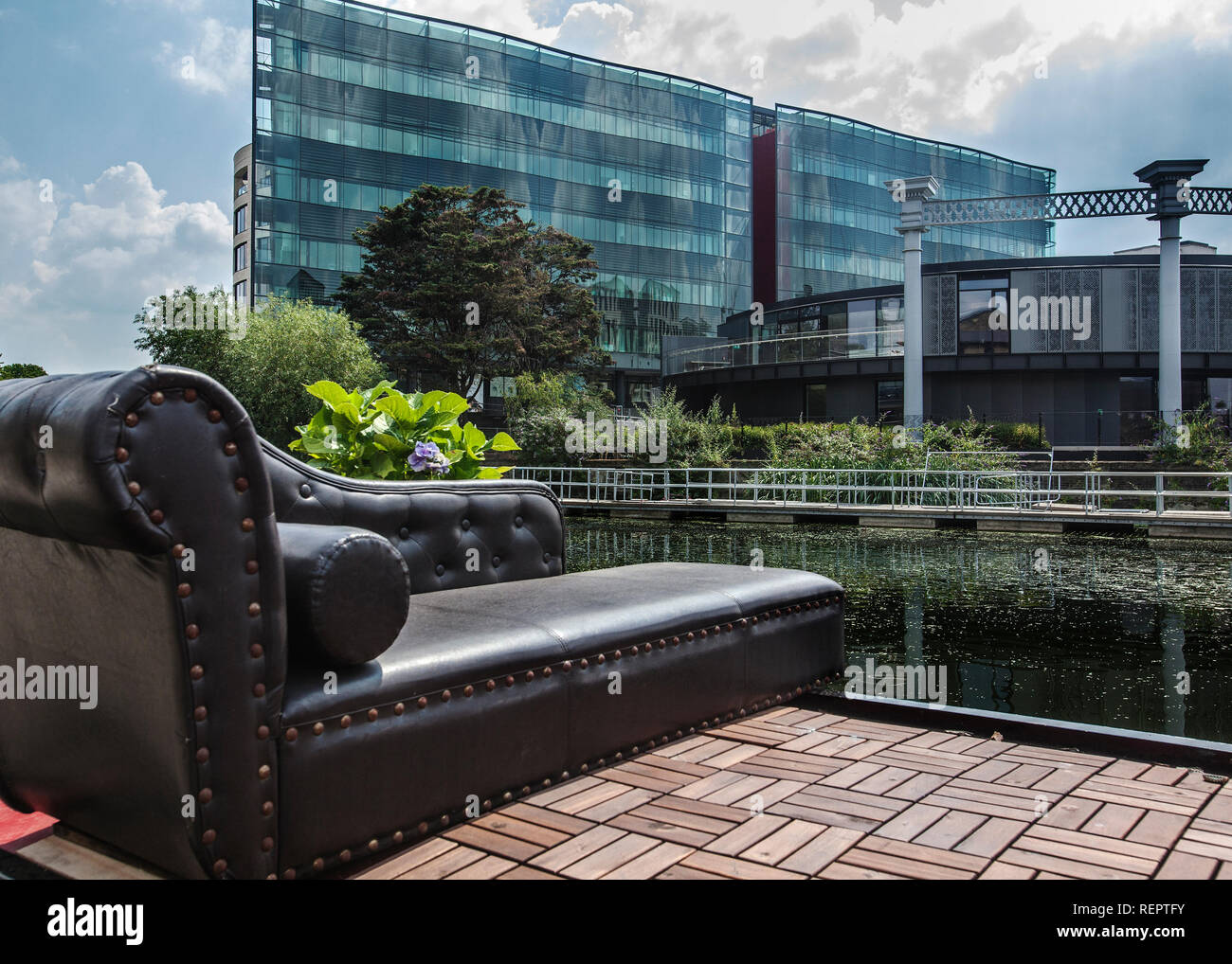 chaise lounge in leather on house boat with the steel and glass kings cross development behind - Stock Image