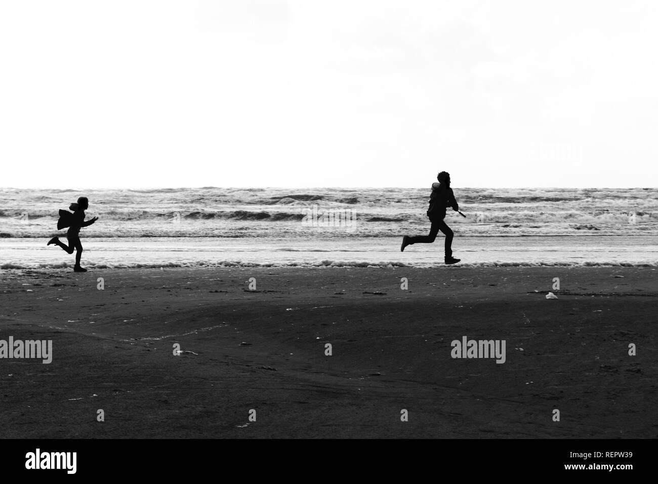 Silhouettes of a brother and a sister running wild and free at the beach. - Stock Image