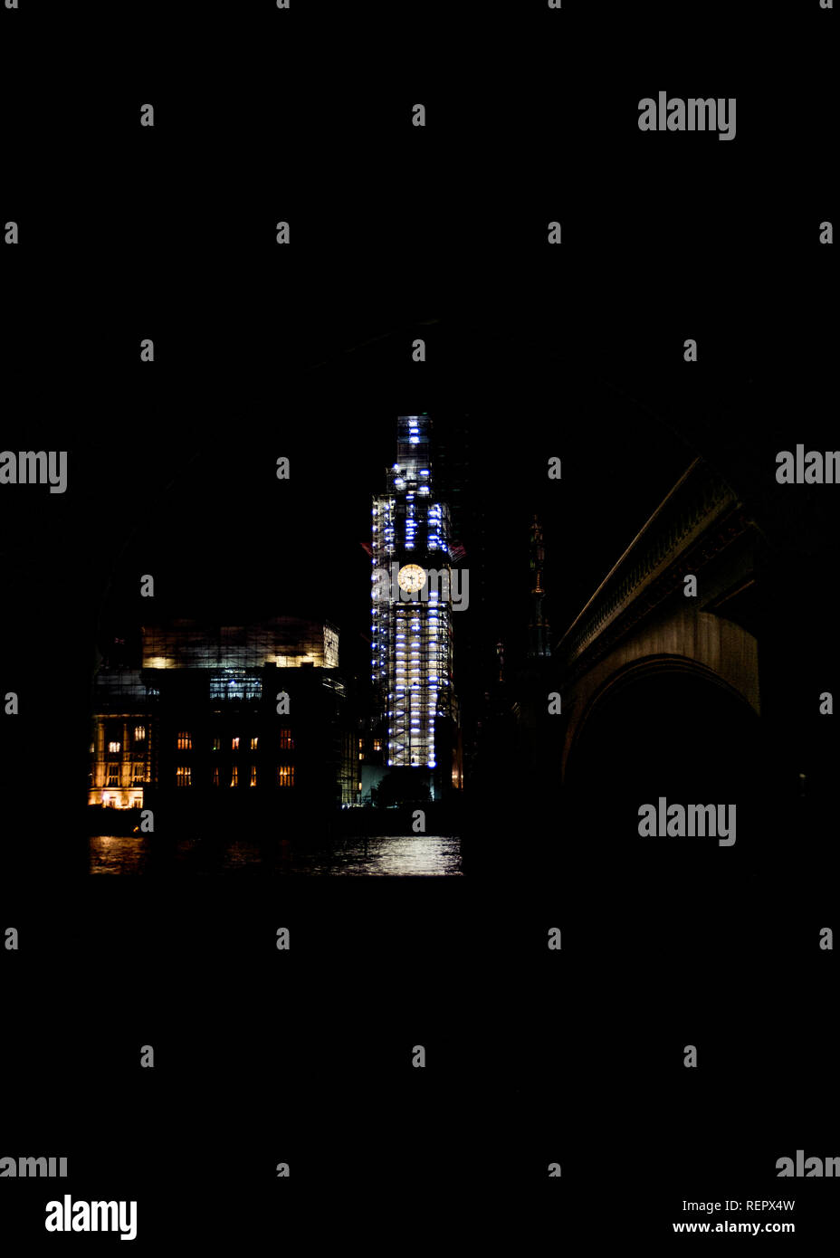 clock tower of houses of parliament Westminster, under scaffolding at night - Stock Image