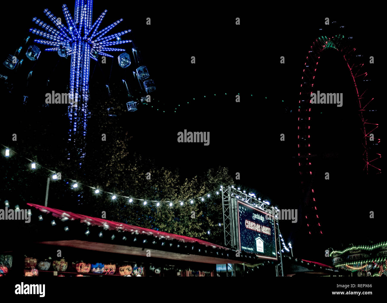 night time at christmas fun fair on south bank London, carousel and amusement rides - Stock Image