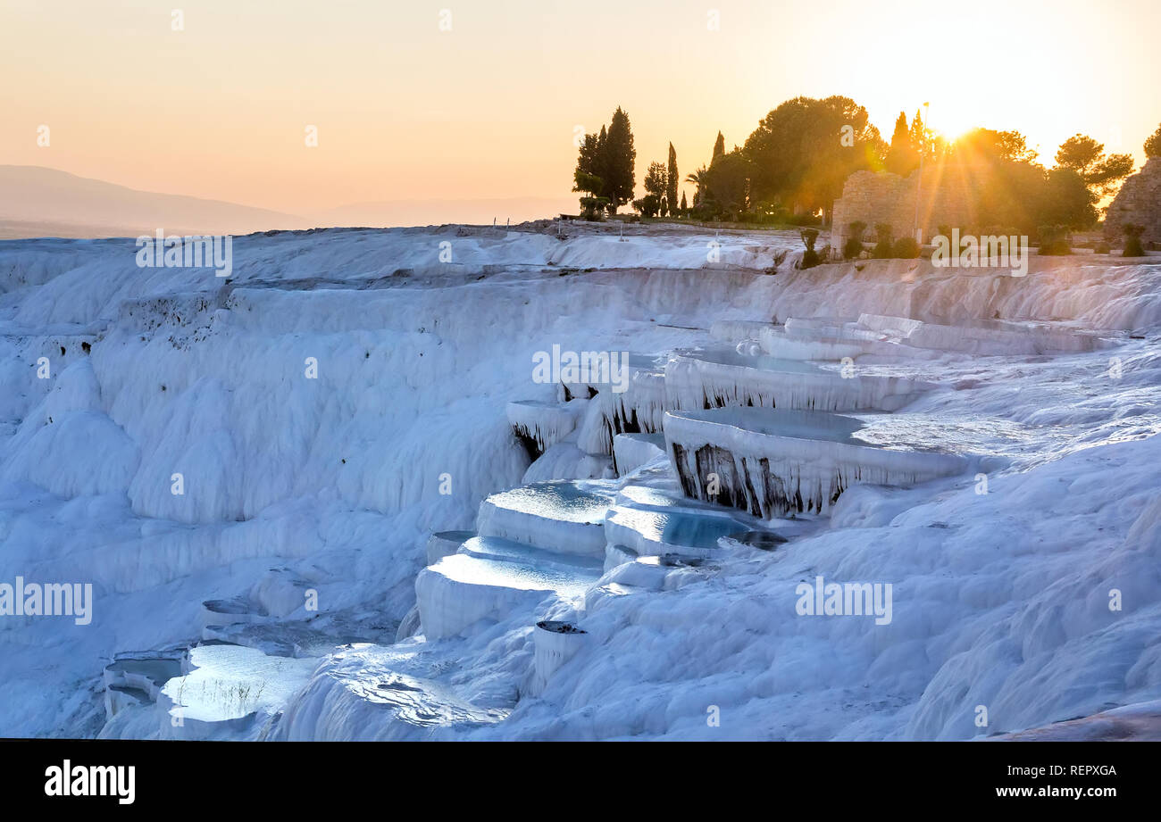 Pools of Pamukkale in Turkey in sunset, contains hot springs and travertines, terraces of carbonate minerals left by the flowing water, UNESCO World H - Stock Image