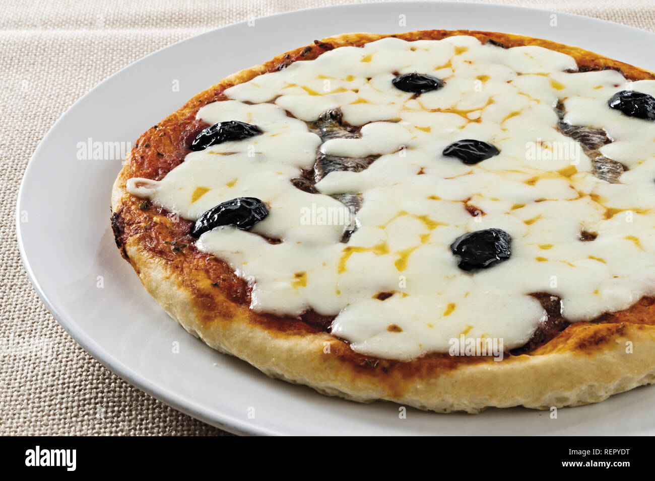 pizza tomato black olives anchovies whole cheese - Stock Image