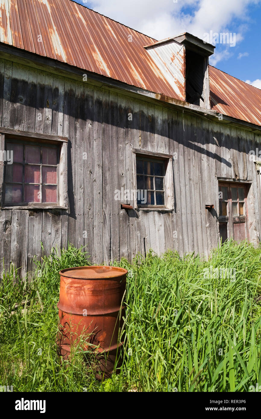 Old grey wooden barn with rusted metal roof and oil drum - Stock Image