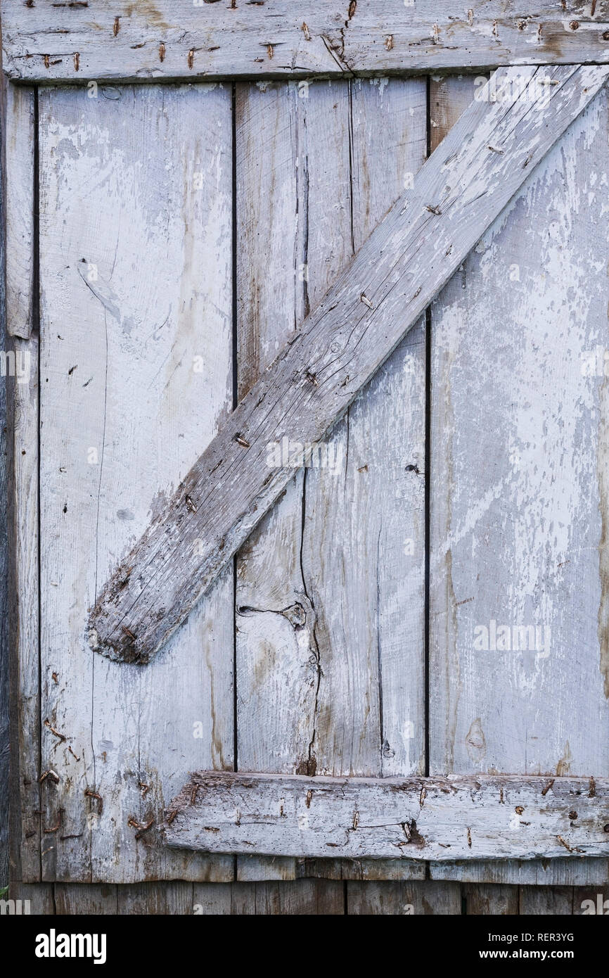 Faded white painted and grey wooden door on the side of a barn - Stock Image