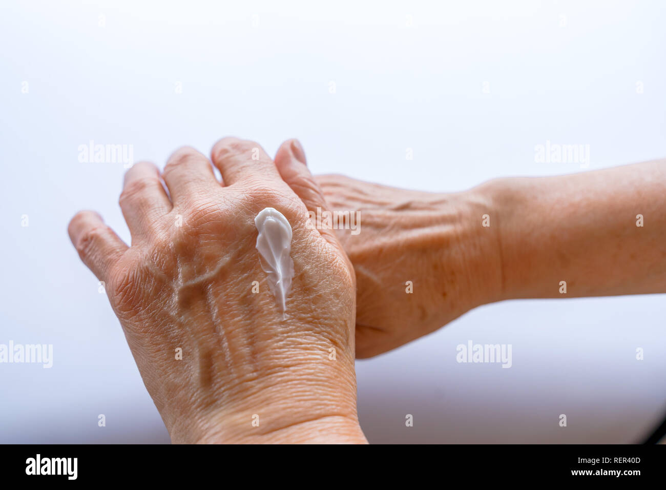 Skin care. Elderly woman applies Cream On Her Hands. Beauty product. - Stock Image