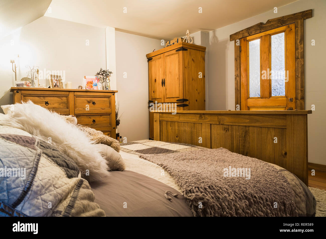 Queen size bed with pinewood footboard, dresser and armoire in upstairs master bedroom inside an old 1839 Canadiana cottage style home - Stock Image
