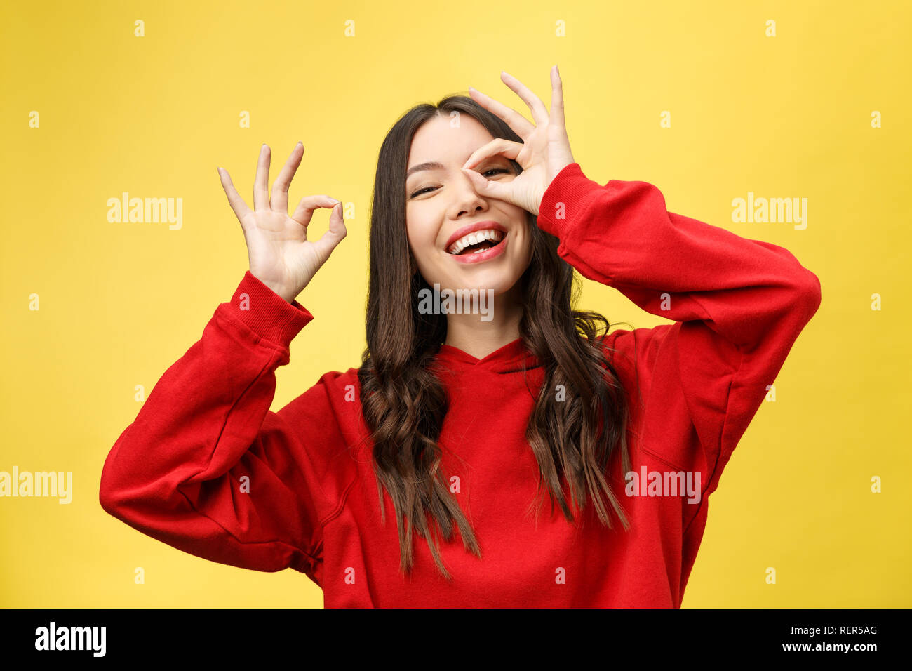 Close up portrait of beautiful joyful Caucasian female smiling, demonstrating white teeth, looking at the camera through fingers in okay gesture. Face expressions, emotions, and body language Stock Photo
