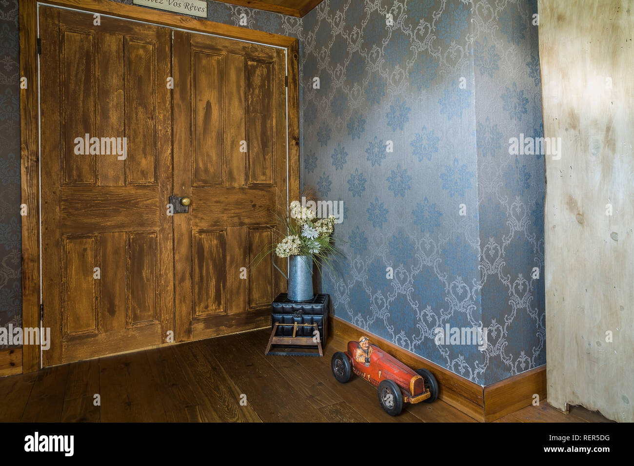 Galvanized watering can with cut flowers and red toy racing car next to brown stained wooden doors in living room inside old 1839 home - Stock Image