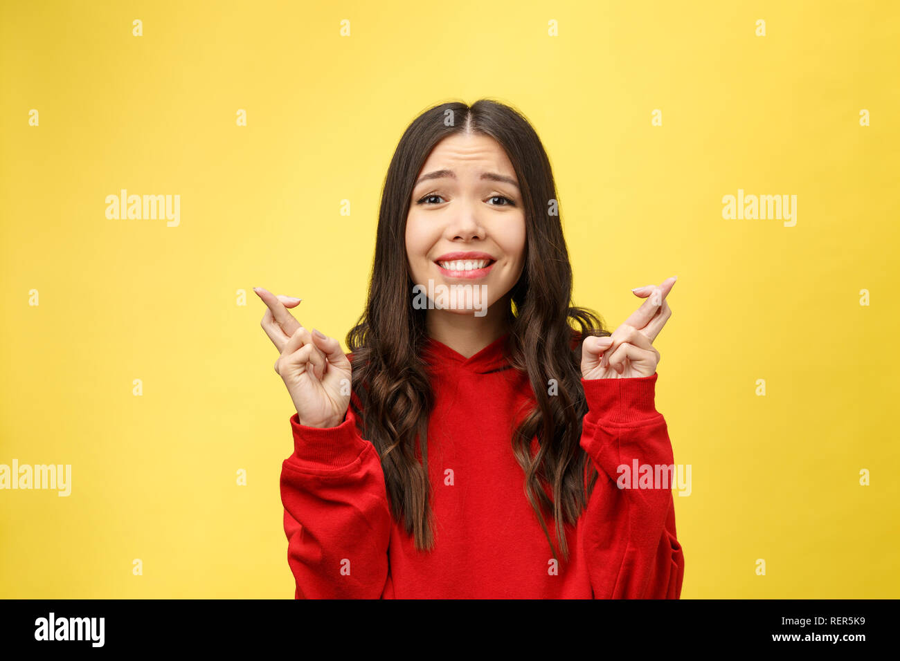 Intrigued woman in praying with crossed fingers and looking away over yellow background - Stock Image