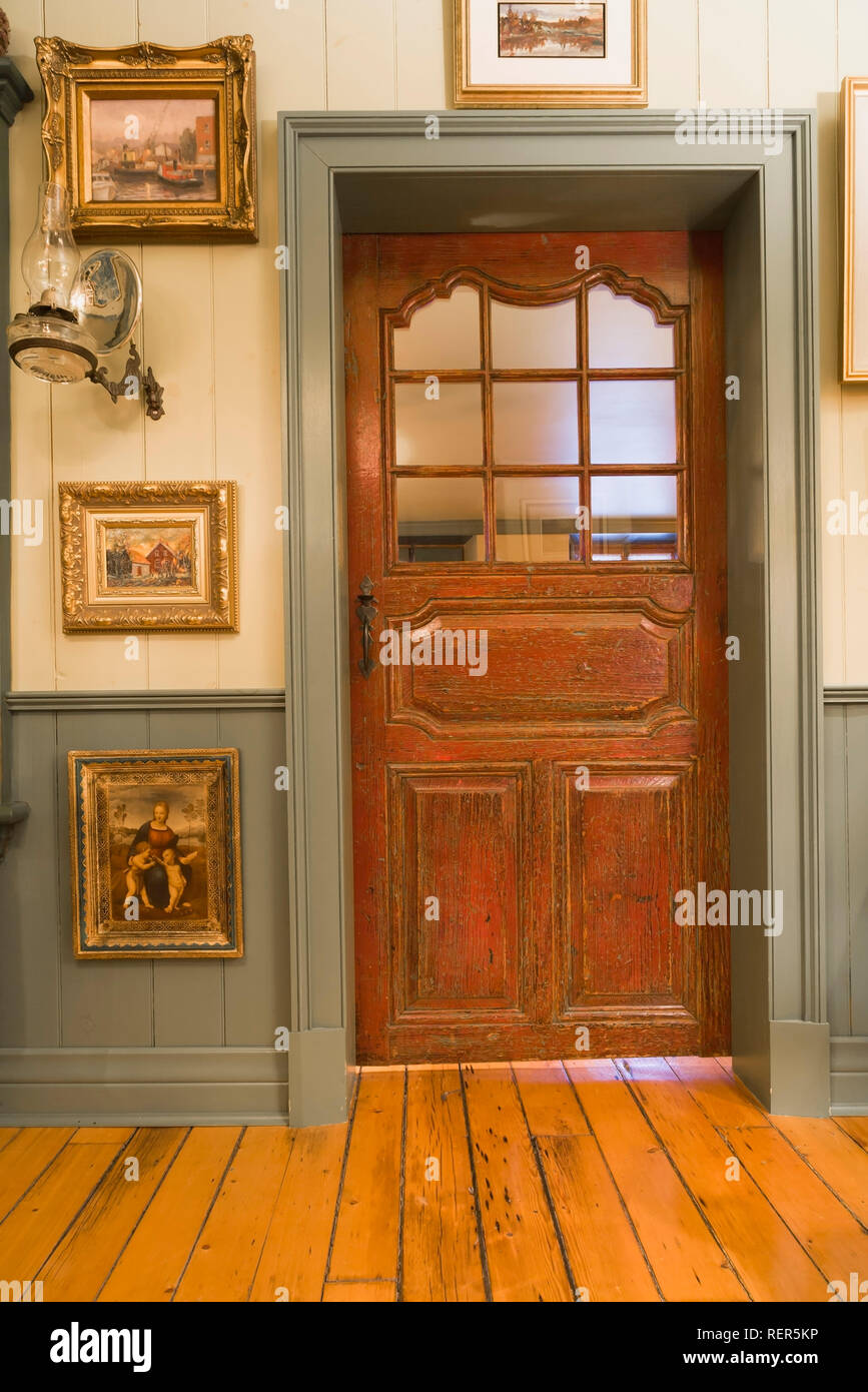 Parlour room decorated with several paintings and closed door leading to living room inside an old circa 1805 Canadiana cottage style home - Stock Image