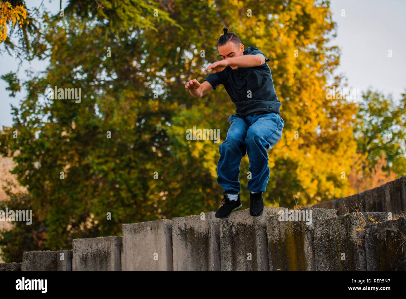 Adult man training parkour while jump over concrete wall Stock Photo