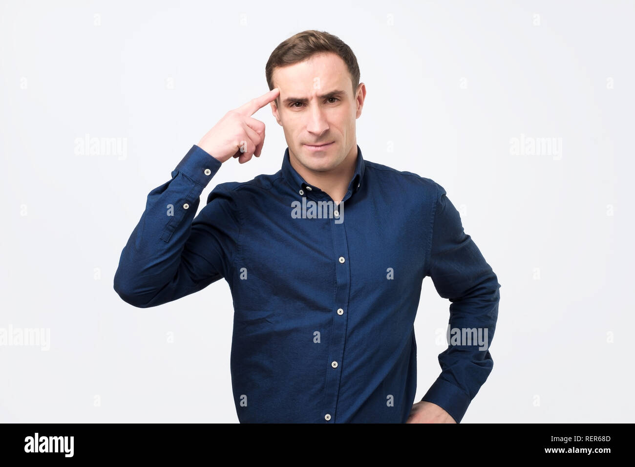 Angry italian man in blue shirt pointing at his temple arguing about job question. - Stock Image