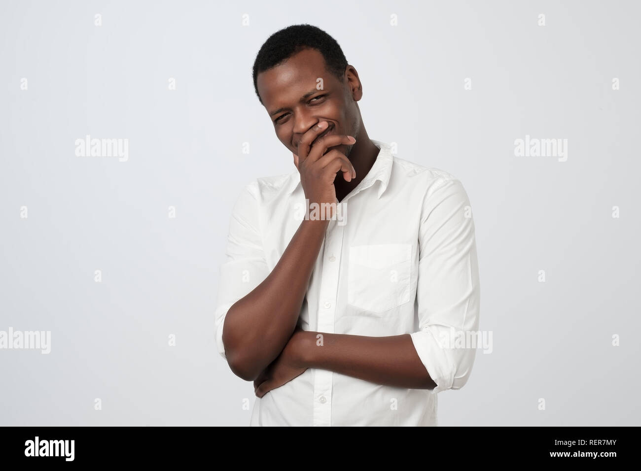 Sly cunning african man touching chin with finger and looking away. Handsome guy thinking. - Stock Image