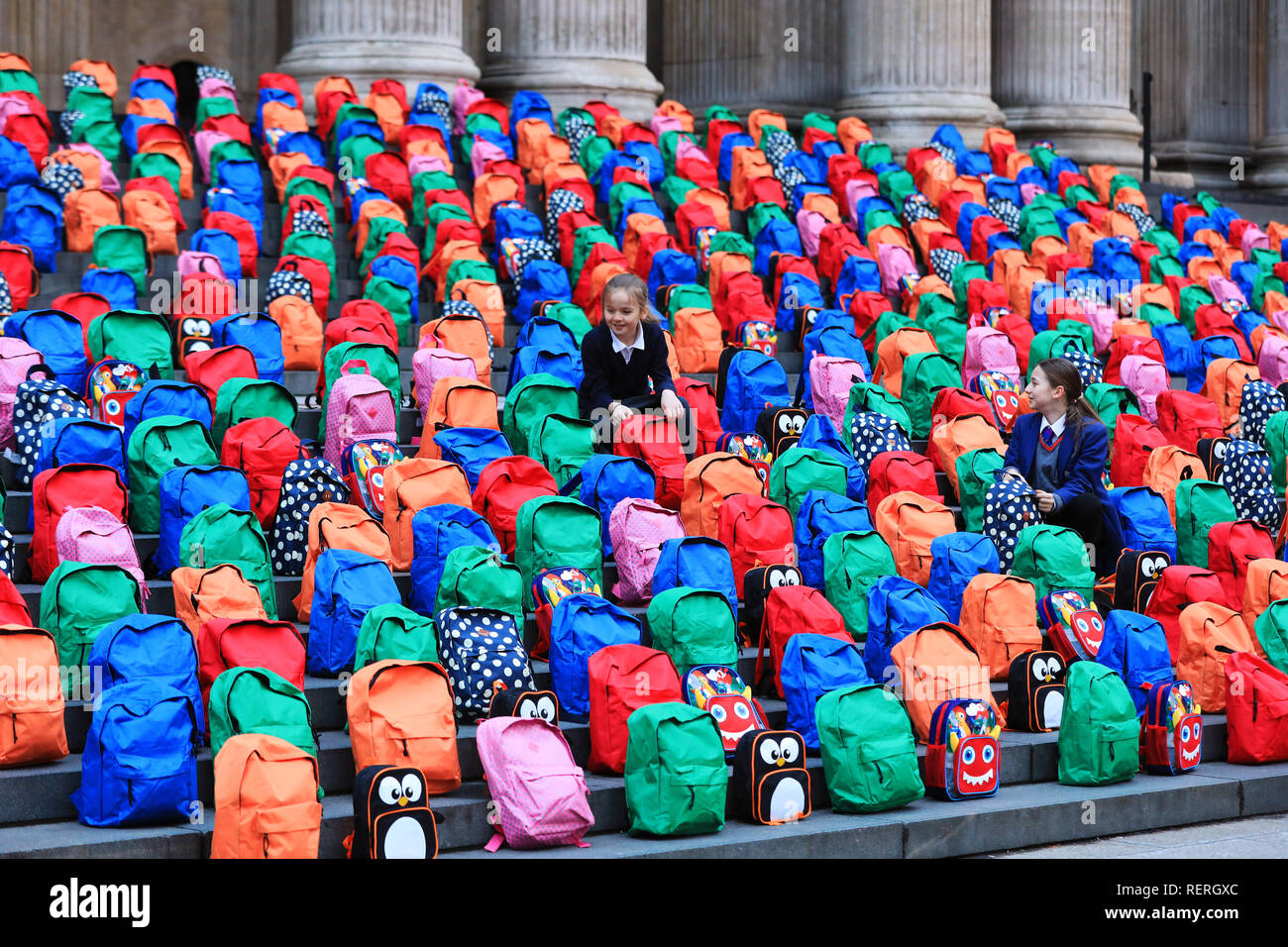 London, UK. 23rd Jan 2019. School children Joana, 9, and sister Jessica, 11, from London look at the 800 schoolbags laid by WaterAid on the steps of St Paul's Cathedral in a moving tribute to the number of children who die every day from dirty water, never reaching their fifth birthday or first day at school. WaterAid placed 800 children's schoolbags on the famous steps of St Paul's Cathedral today as a stark reminder of the number of young children's lives lost every single day due to dirty water and poor sanitation. Credit: Oliver Dixon/Alamy Live News Stock Photo