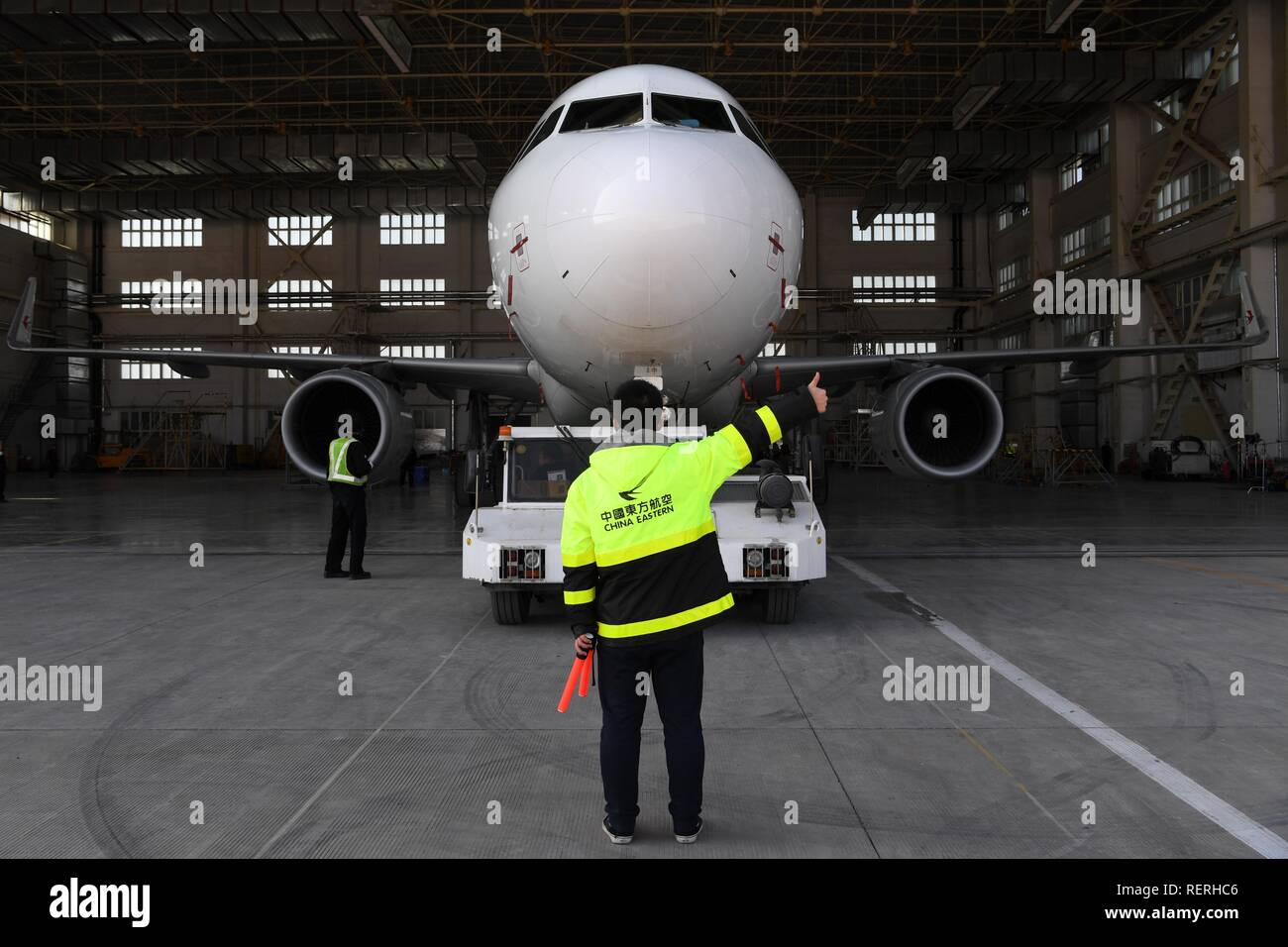 (190123) -- BEIJING, Jan. 23, 2019 (Xinhua) -- A mechanic of China Eastern Airlines guides the repaired aircraft out of the warehouse at Zhongchuan International Airport in Lanzhou, capital of northwest China's Gansu Province, Jan. 31, 2018. China's civil aviation industry is accelerating its advance into the digital era, with major players sending clear signals of new opportunities worldwide. (Xinhua/Fan Peishen) Stock Photo