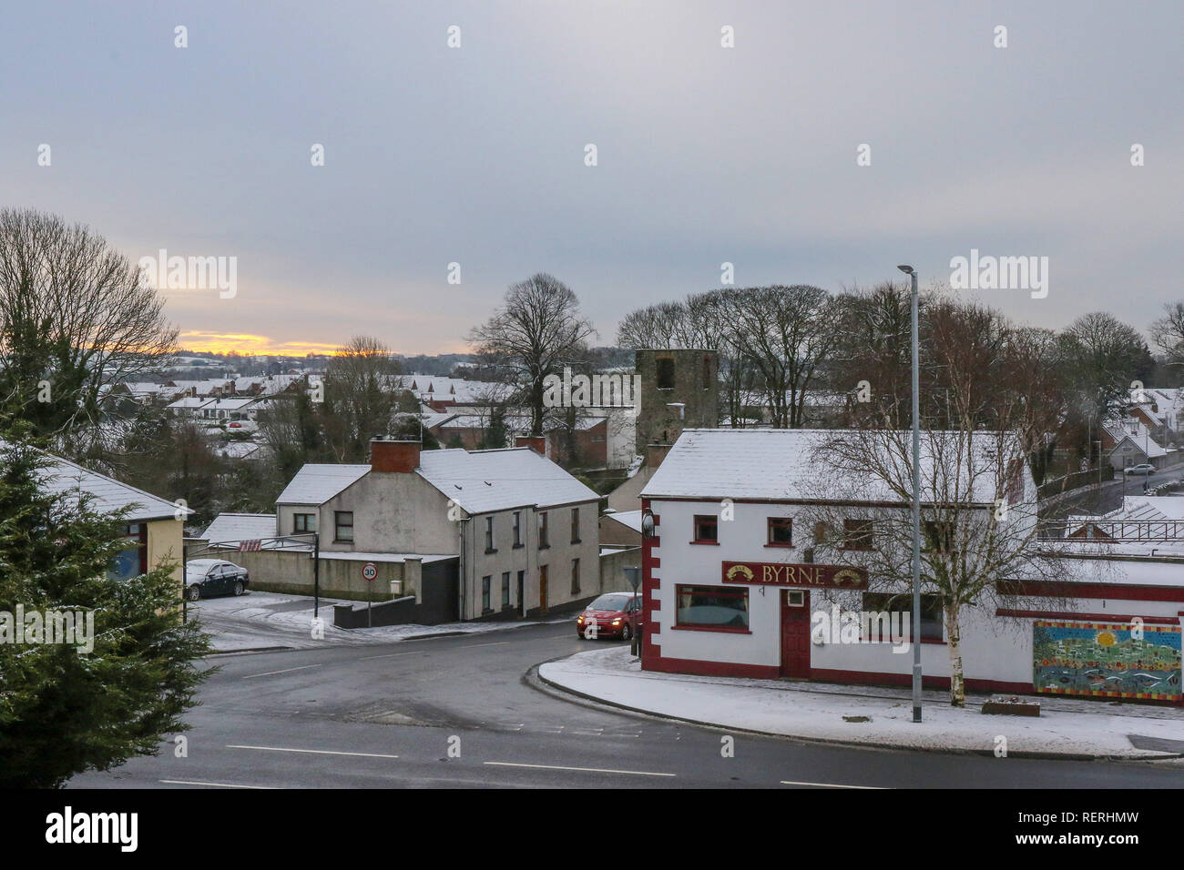 Magheralin, County Armagh, Northern, Ireland. 23rd Jan, 2019. Snow and ice made for tricky driving conditions off main roads. Sun rising over snow-covered hills to the east of the village. Credit: David Hunter/Alamy Live News - Stock Image