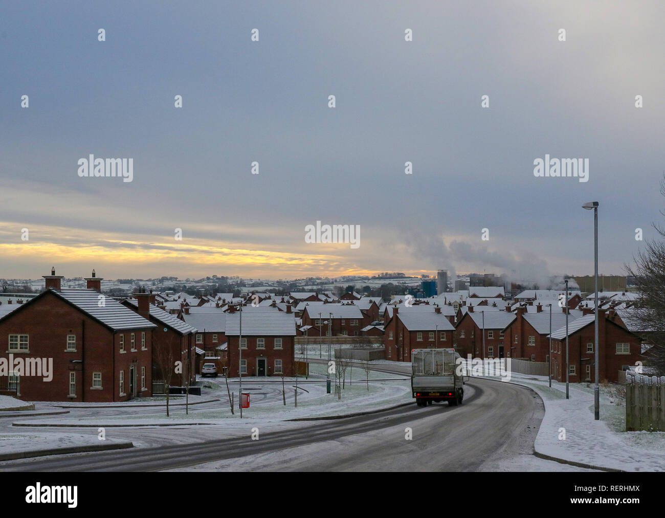 Magheralin, County Armagh, Northern, Ireland. 23rd Jan, 2019. Snow and ice made for tricky driving conditions off main roads. Sun rising in the east of the village beyond the cheese plant. Credit: David Hunter/Alamy Live News - Stock Image