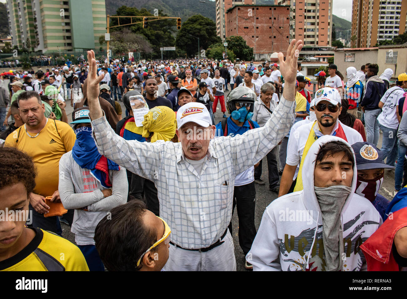 Caracas, Venezuela. 23rd Jan, 2019. A man raises his arms in a protest against the government of President Maduro. In the midst of the escalating political crisis in Venezuela, many people took to the streets. Many states, international organizations and the opposition no longer recognize Maduro as a legitimate head of state. According to observers, his re-election last year did not take place under free and fair conditions. Credit: Rayner Pena/dpa/Alamy Live News - Stock Image