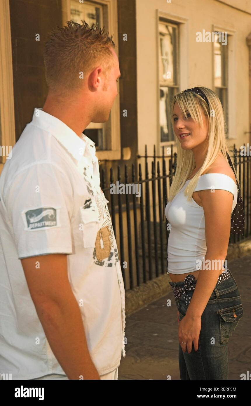 Young man turns to look at attractive young woman passing him in the street - Stock Image