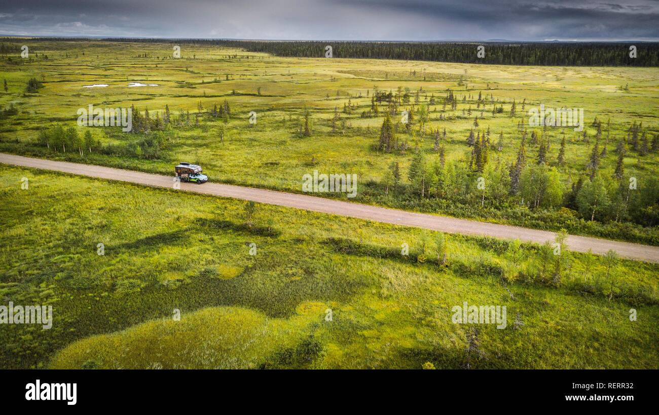 Drone view, aerial photo, motorhome (Ford Ranger with body Oman) on gravel road in wetland, bog with boreal, arctic conifers - Stock Image