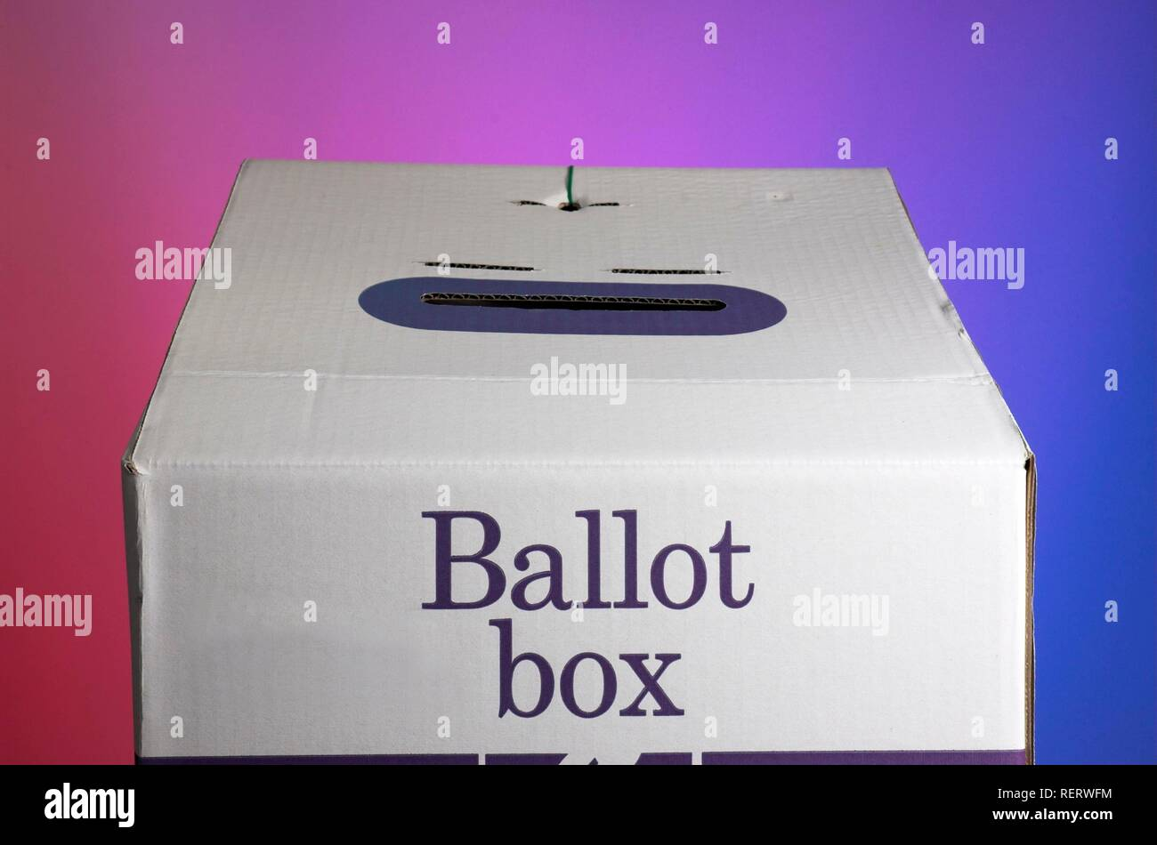 Ballot box against backdrop with opposing colours of the political spectrum - Stock Image