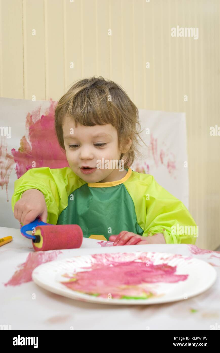 A two year old girl in a plastic smock painting in a playroom with a brush and roller Stock Photo