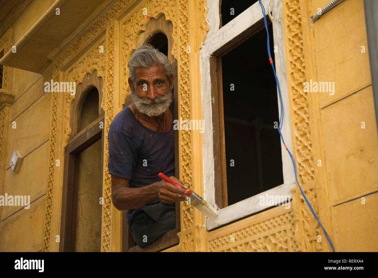 Indian painting a yellow house, Jaisalmer, Thar Desert, Rajasthan, India, South Asia - Stock Image