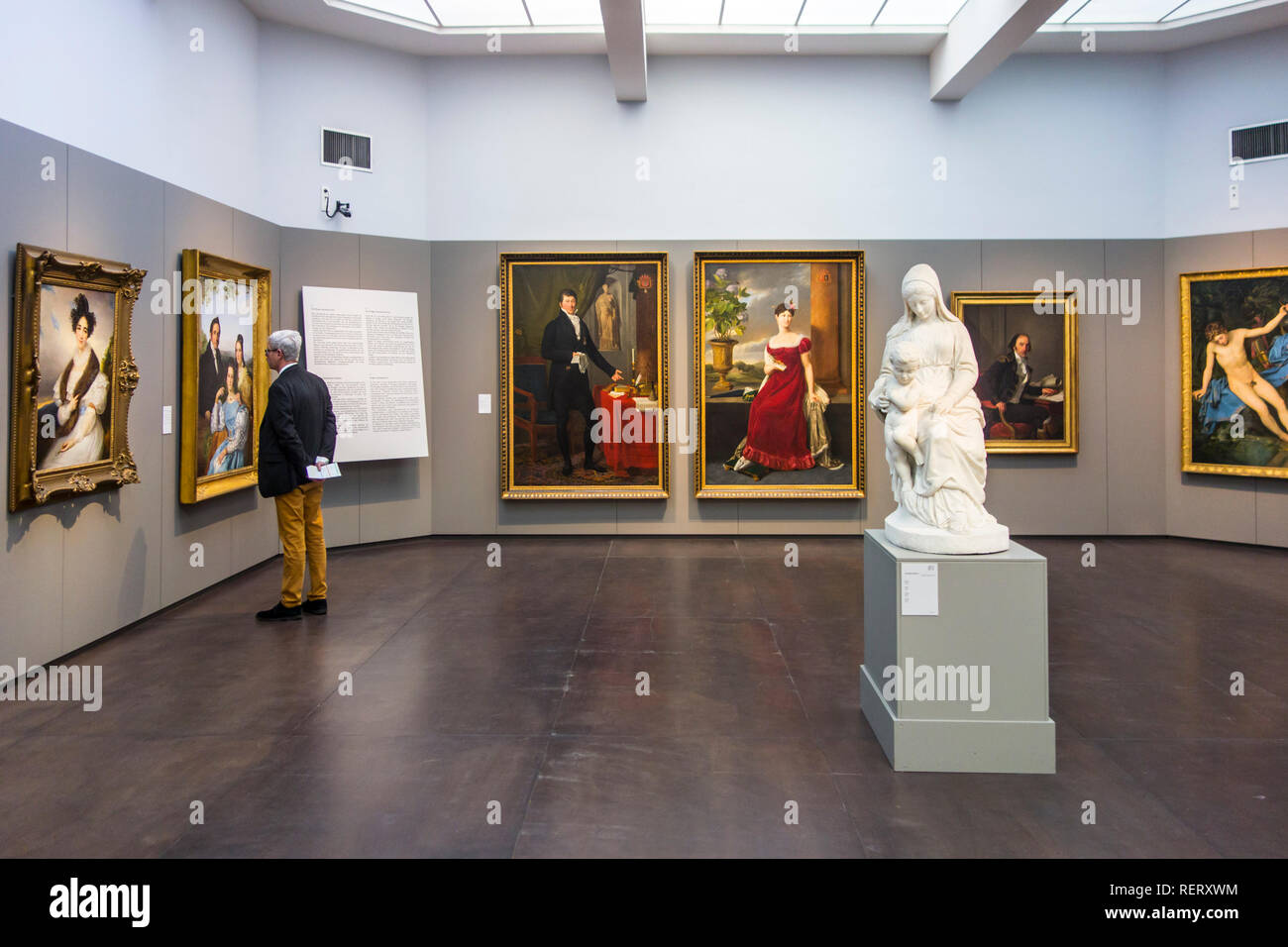 Visitor looking at 19th century Neoclassical paintings in the Groeningemuseum, Fine Arts Museum in the city Bruges, West Flanders, Belgium - Stock Image