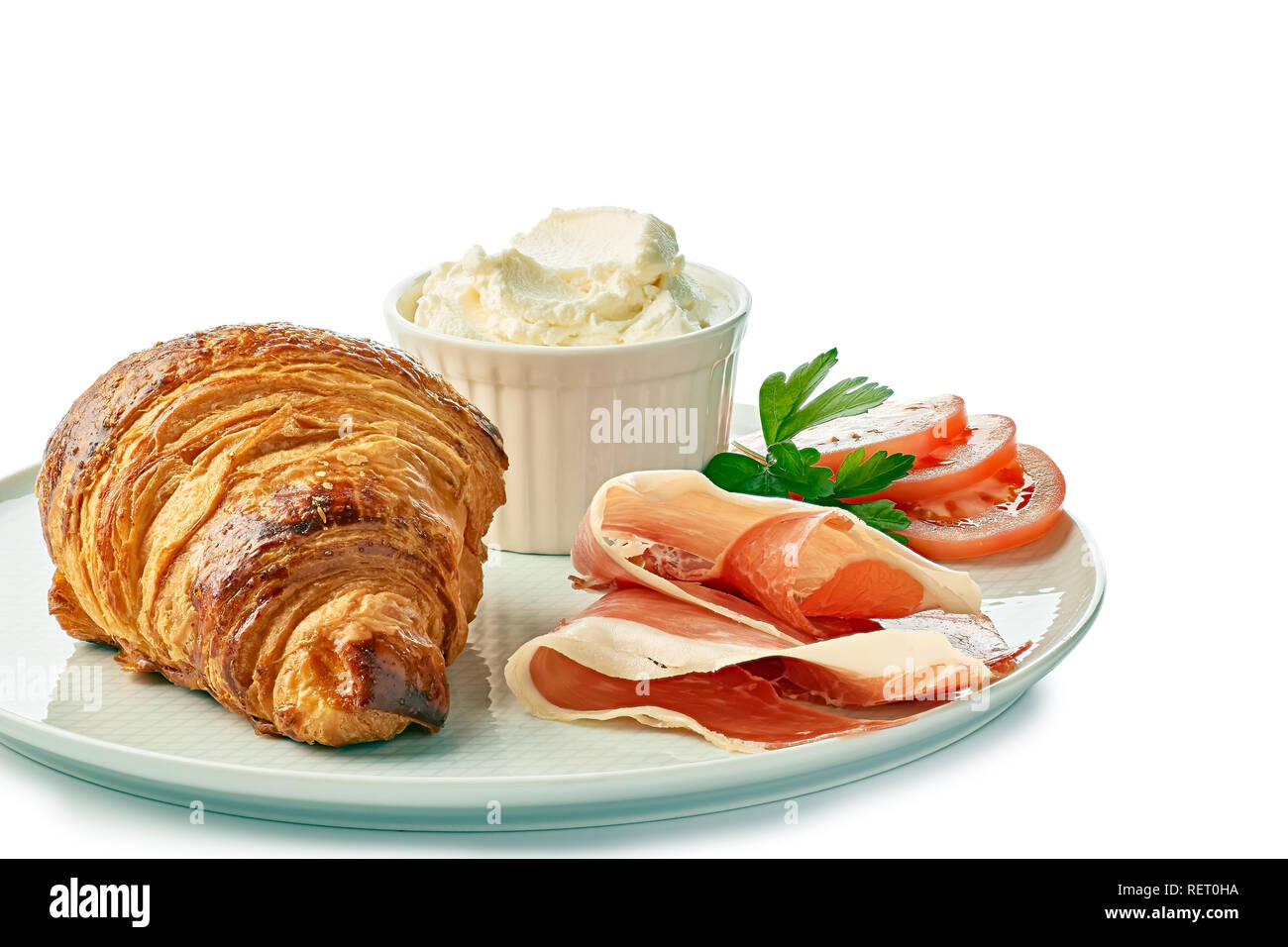 Dish with croissant creame cheese and jamon on white - Stock Image