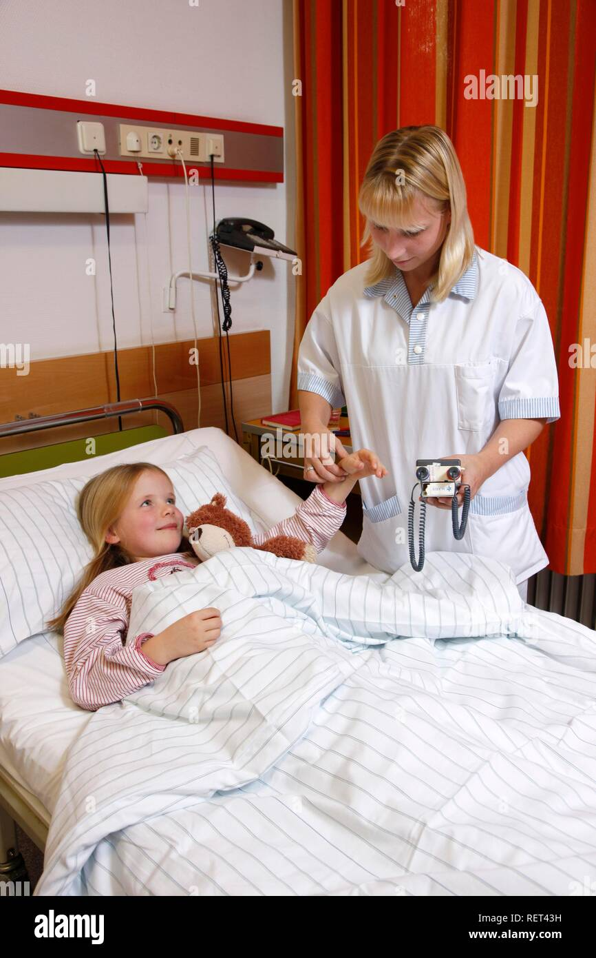Nurse taking pulse rate of a young patient, 7 years, in hospital - Stock Image