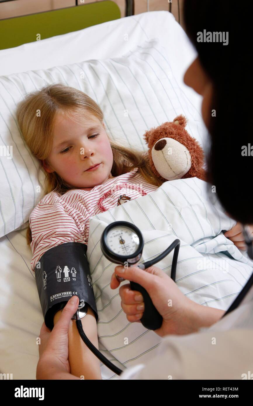 Nurse measuring blood pressure of a young patient, 7 years, in hospital - Stock Image