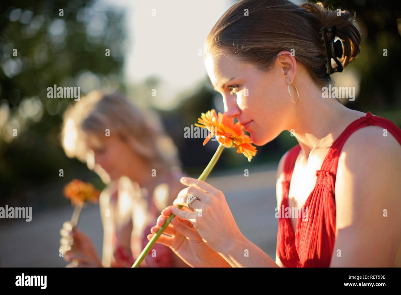Young woman smelling an orange flower while sitting next to her friend in the sunshine. - Stock Image