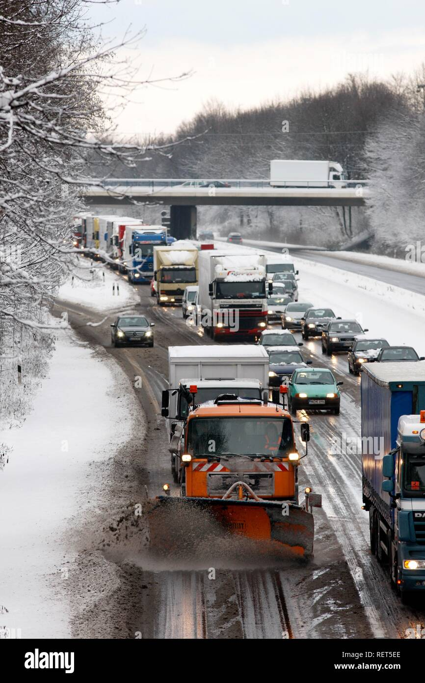 Snow plough in operation, traffic jam after heavy snow fall, motorway Autobahn A40, Ruhr expressway between Duisburg and Essen - Stock Image