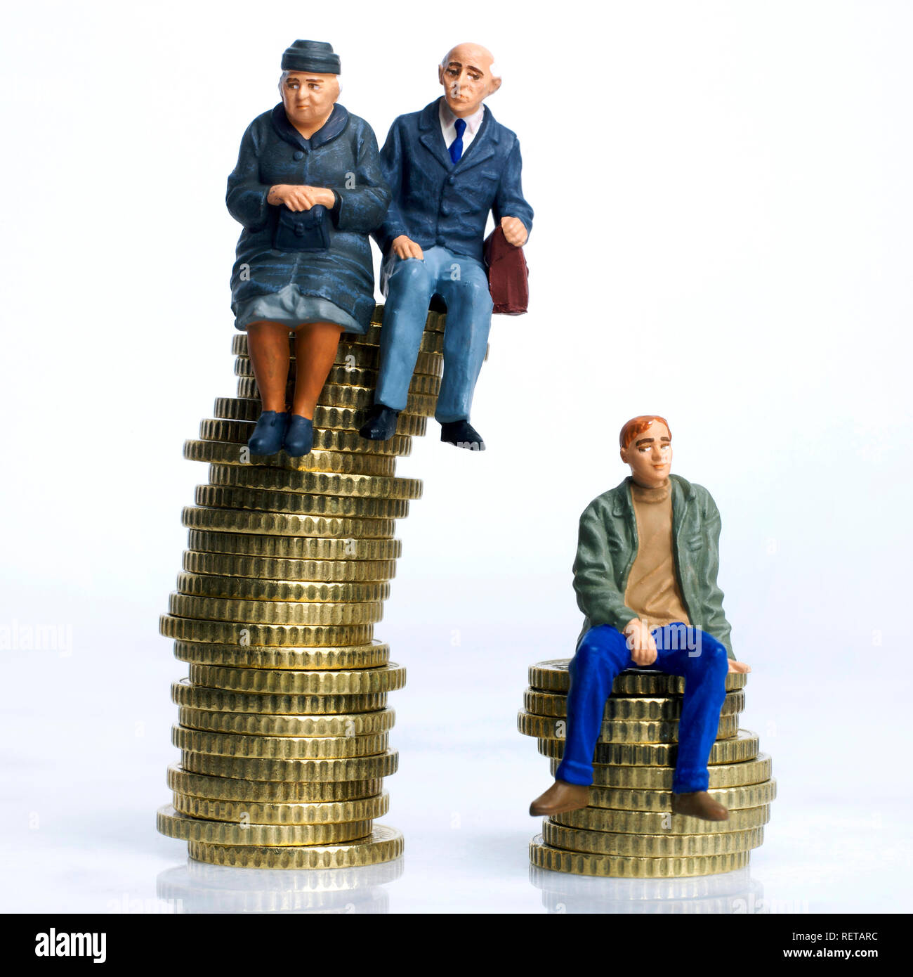 Symbol picture pension, Elderly couple and young man, figurines sitting on stack of coins - Stock Image