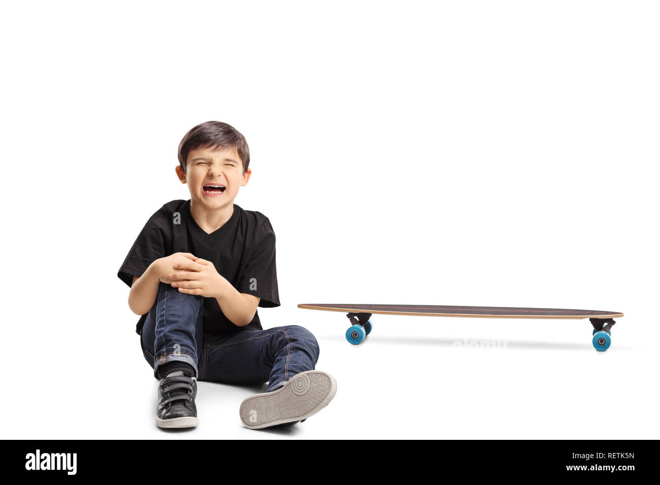 A boy with an injured knee sitting next to a longboard isolated on white background - Stock Image