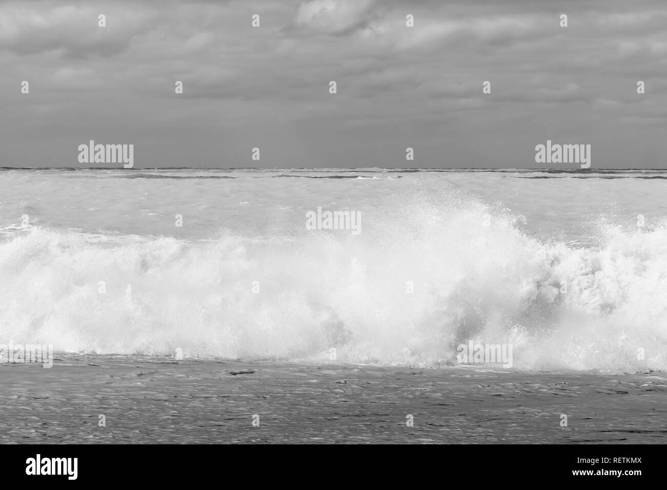 Large dangerous breaking waves on shingle foreshore at Birdlings Flat on Banks Peninsula New Zealand - Stock Image