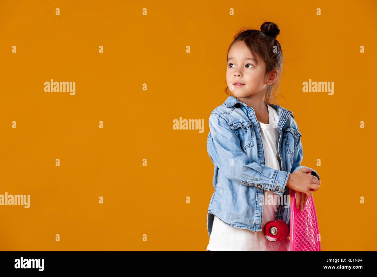6c2317d78e4a Stylish little child girl with skateboard in denim on orange background -  Stock Image