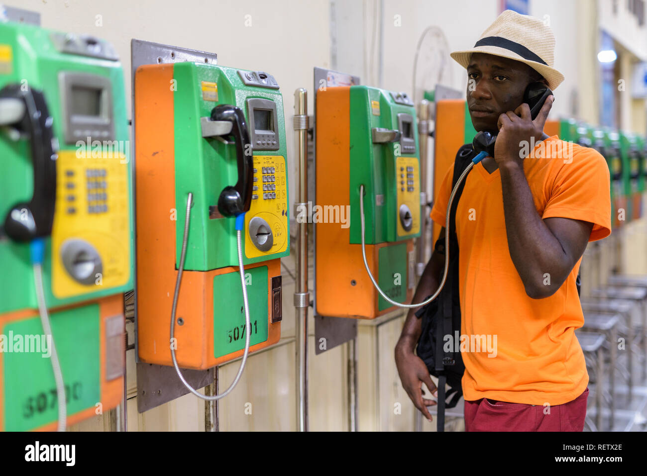 African tourist man talking on payphone and thinking - Stock Image