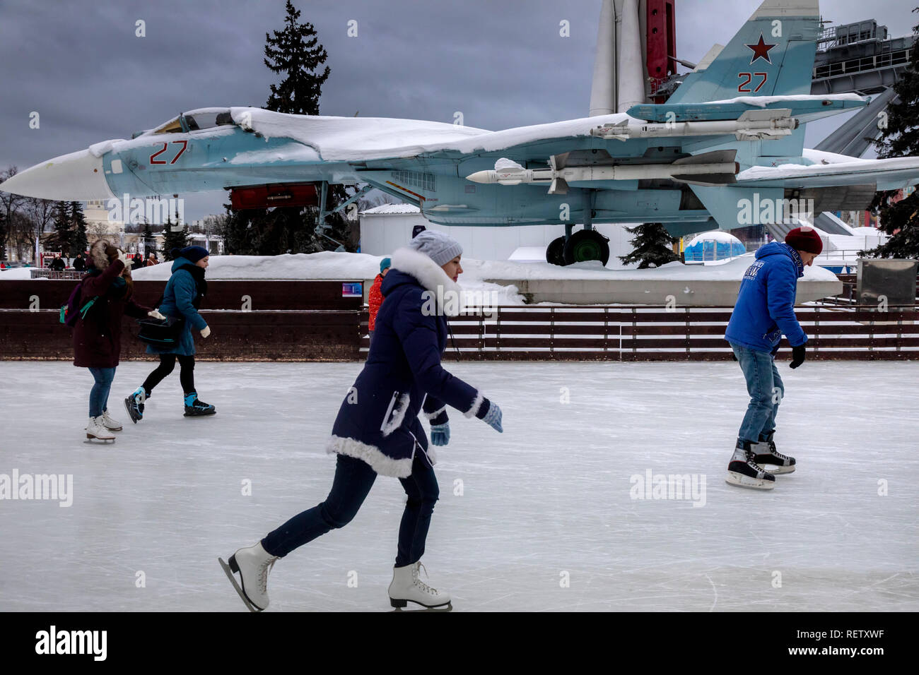 People skate on the ice rink on the background of the Sukhoi Su-27 fighter aircraft in the Industry Square at VDNKh in Moscow, Russia - Stock Image