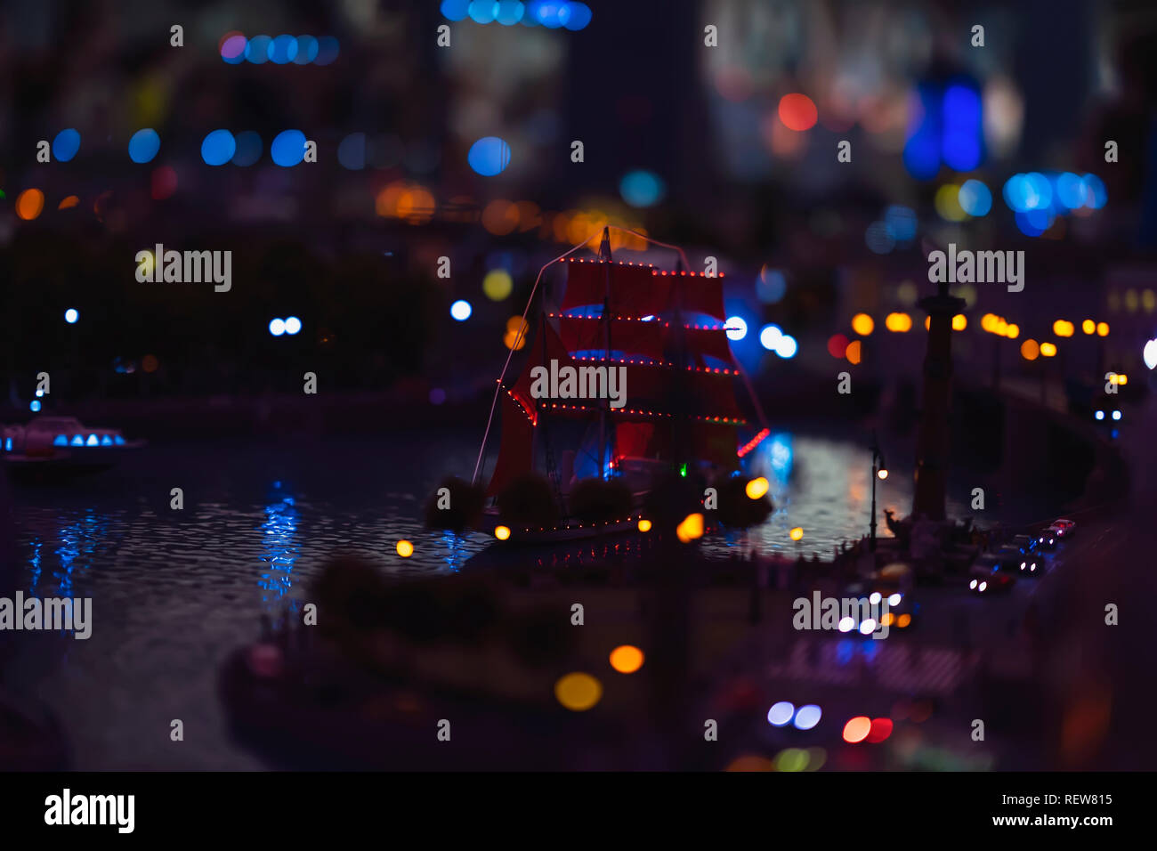 Night bokeh, defocused city light with sailboat at the pier, realistic miniature, abstract blurred background - Stock Image