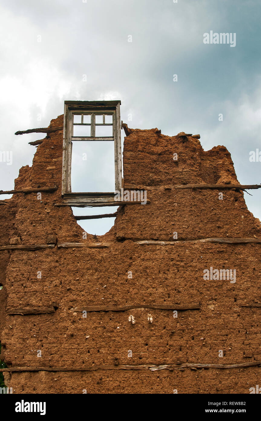 Brick wall with adobe clay plaster and broken wooden window frame remained of ruined old rural country house on cloudy blue sky background - Stock Image