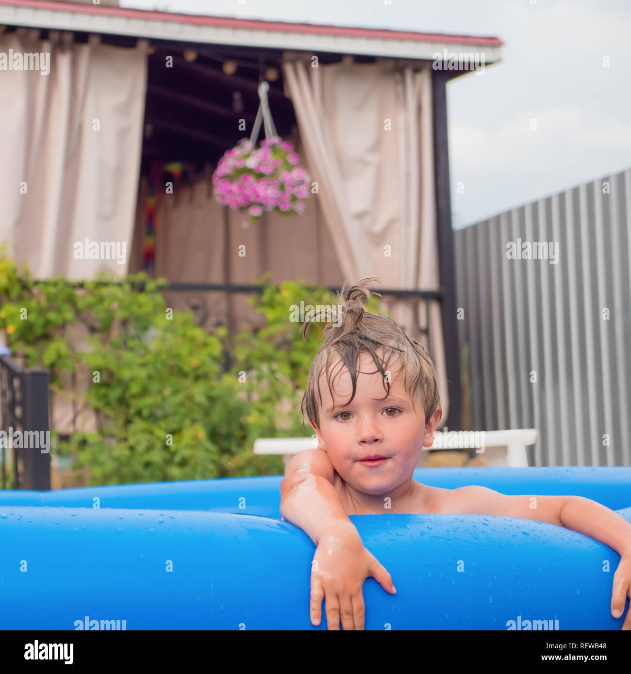 Boy playing in water pool. Water pool on front, back yard. Water games. Cheerful children playing in water. Happy children spending time in summer. Tr - Stock Image